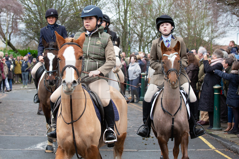 © Licensed to London News Pictures. 01/01/2019. Atherstone, North Warwickshire, UK. Atherstone Hunt meet in the Market Square, Atherstone Town Centre, Warwickshire. The traditional New Year's Day Hunt starts at Noon with speeches and a drink for the Huntsmen and women. Riders of all ages took part in the meet and there were protests from Anti Hunt protestors who had positioned themselves in the centre of the Market Square. The Hunt then formed up and rode from the town centre passing huge New Year's Day crowds that had come to see the spectacle. Photo credit: Dave Warren/LNP