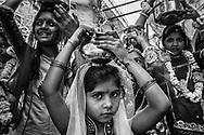 Young women get ready to start a parade celebrating the Gargaun festival in Jodhpur. This festival honors the union of the god Shiva with the goddess Parvati. Women celebrate by dressing very colorful and carrying pots of sacred water in parades through the streets. Jodhpur, Rajhastan, India / Un grupo de mujeres jóvenes se preparan para inicar un desfile por festival de Garguan en Jodhpur. Este festival honra la unión del dios Shiva con la diosa Parvati. Las mujeres lo celebran vistiéndose de una manera muy vistosa y cargando recipientes de agua sagrada en desfiles por las calles. Jodhpur, Rajastán, India.