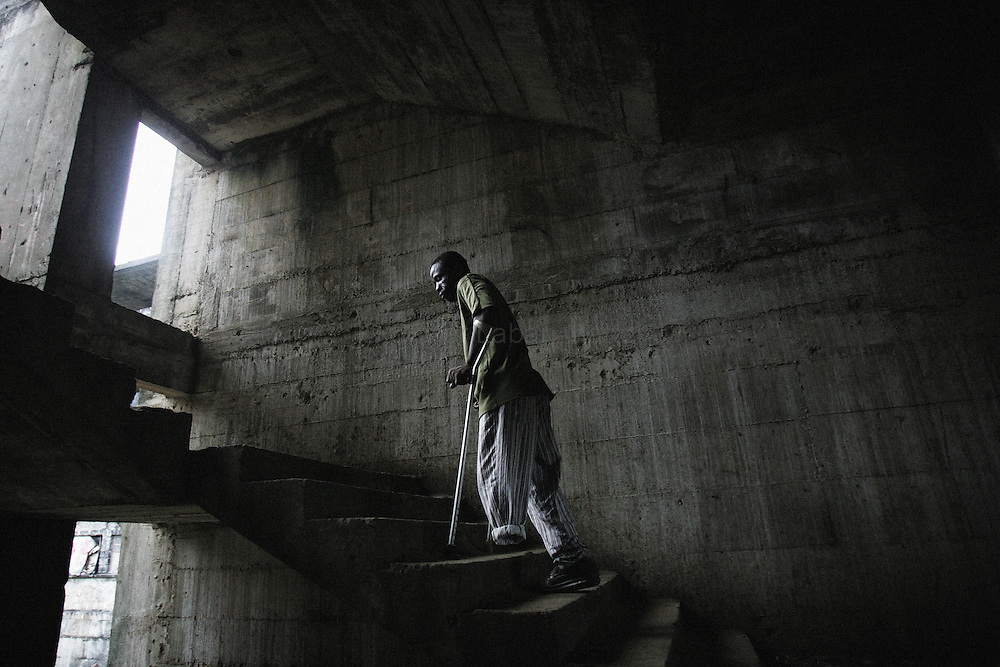 """Lieutenant Joseph Kpayon Chea walks up stairs 19 September 2005 at the former uncompleted Ministry of National Defense building in Congo Town on the outskirts of Monrovia. Chea is still a soldier and earns $890 Liberian dollars ($14USD) monthly which he uses to support his wife and 7 children. The """"Pentagon"""", named this way by its occupants, shelters 394 families totalling approximately 3,000 people who were booted out in May 2005 of the Barclay Training Center, which had been their home for the last two decades. Former soldiers, who fought for former Liberian presidents Samuel Doe and Charles Taylor, live in this building with no water or electricity, overcoming past differences. The construction of the building started in 1984 under Doe's leadership, and the war interrupted the its completion and later served as a base for Taylor's men."""