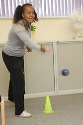 Day Service user throwing a ball whilst taking part in indoor bowls,