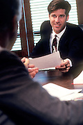 Businessman handing paper to collegue across table.