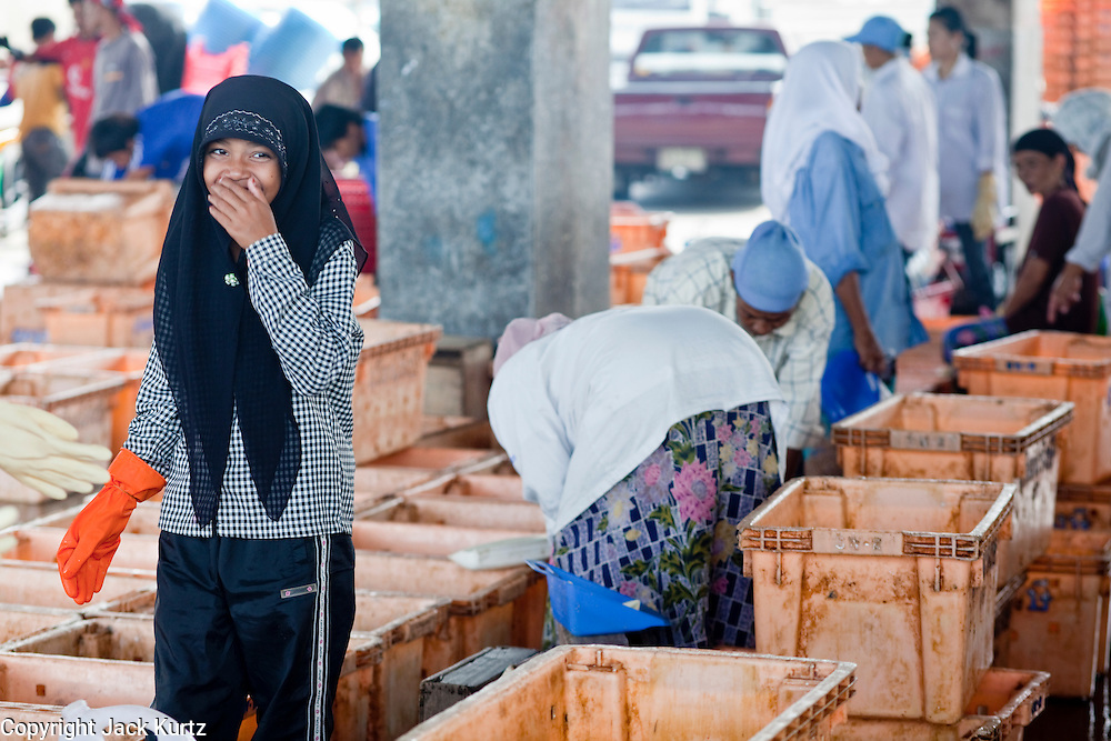 Sept. 27, 2009 -- PATTANI, THAILAND:   Muslim women wait to start work sorting fish in the fishing port in Pattani, Thailand, Sept. 27. Fishing is the main industry in Pattani, one of just three Thai provinces with a Muslim majority. Thousands of people, mostly Buddhist Thais and Burmese Buddhist immigrants, are employed in the fishing industry, either crewing ships, working in processing plants or working in the ship building and refreshing yards.  Photo by Jack Kurtz / ZUMA Press
