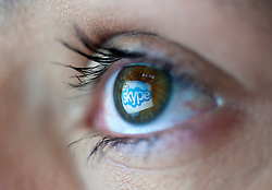 Skype internet telephone and video website logo reflected in womans eye from computer screen