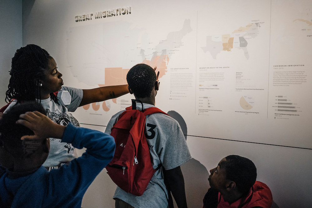 Sixth-graders from Knowledge Is Power Program (KIPP) DC, including Tyron Proctor, 11, Omari Sterling, 11, Tay'sean Barrow, 12, and their teacher Gabrielle Randall, look at a map of the great migration inside the Smithsonian National Musuem of African American History and Culture during their visit on Oct 21, 2016. The students spent an hour touring the new Washington, D.C. museum, which is only available to see with reserved tickets during the first year.