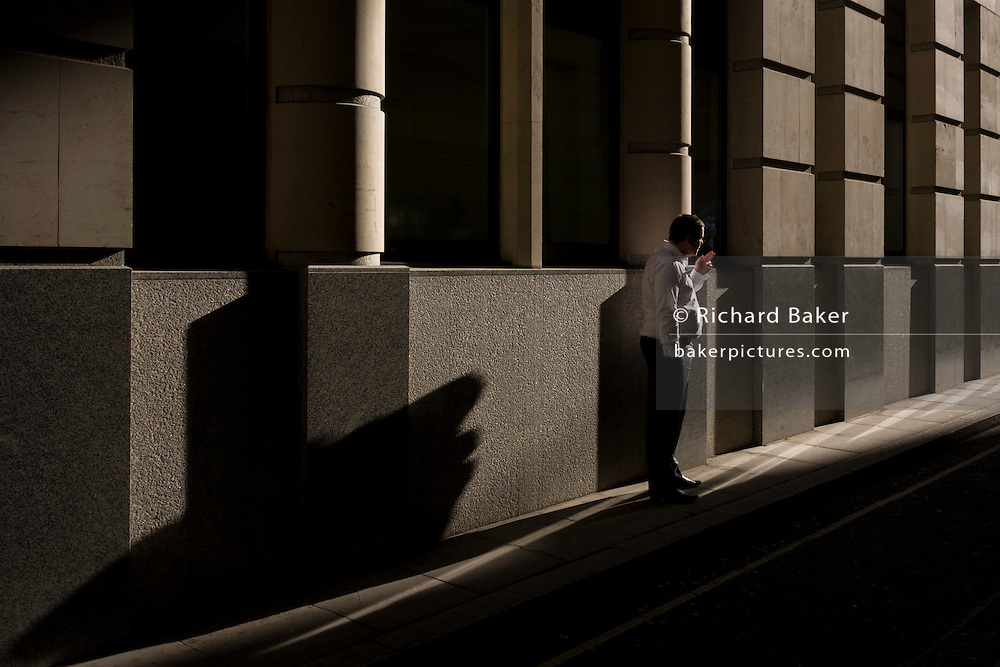 A city office worker pauses during a busy day for a quiet moment peace with a cigarette in a London sidestreet.