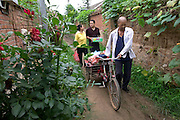 (MODEL RELEASED IMAGE). Loaded down with groceries for the family portrait, Li Jinxian and Cui Haiwang are met by Grandfather Cui with his sanlun che (three-wheeled cart) at the entrance to the narrow lane leading to their home. The Cui family (indeed, most rural Chinese) would never buy this quantity of food at one time, but would buy smaller quantities every day. Hungry Planet: What the World Eats (p. 87). The Cui family of Weitaiwu village, Beijing Province, China, is one of the thirty families featured, with a weeks' worth of food, in the book Hungry Planet: What the World Eats.