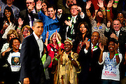 """October 16, 2010 - A crowd applauds President Barack Obama after listening to him speak during a campaign rally for Governor Deval Patrick at the Hynes Convention Center in Boston on Saturday. During his address Obama compared the United States to a car that had been driven into a ditch, which Democrats were trying to push out. """"I thought Obama's story about pushing the car out of the ditch was great. We should keep it in drive,"""" said Andre Mastey, a Democrat who attended the event. Photo by Lathan Goumas."""