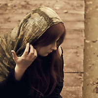 Red hair girl with covered hair by the veil holding hair in her hand sitting by the lake