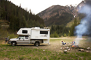 A couple enjoys a fire by their camper.  Near Duffy lake, on the Sea to Sky Highway , British Columbia, Canada