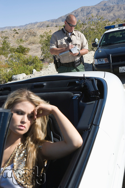 Policeman writing speeding ticket for young woman