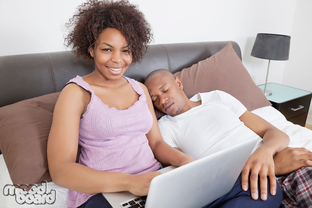 Portrait of happy young woman using laptop while men sleeping in bed
