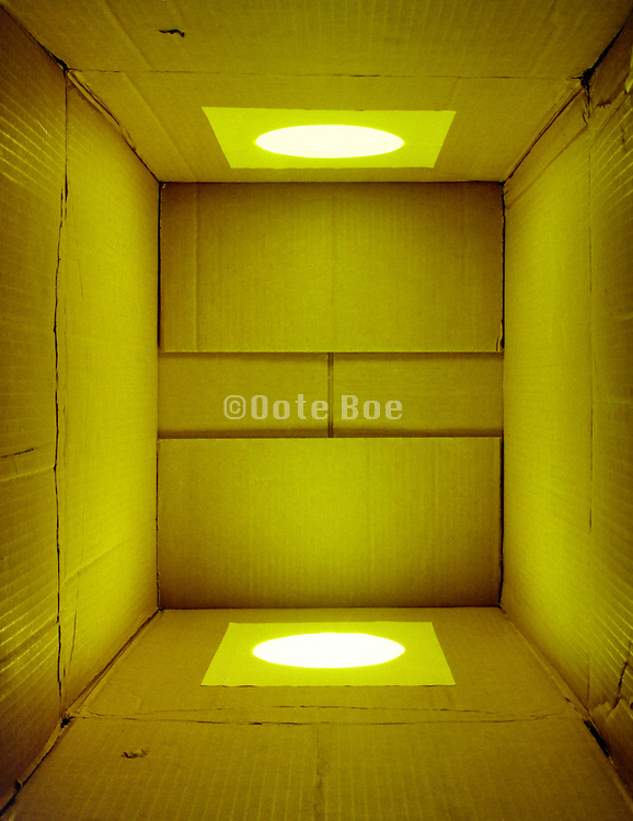 cardboard box with a monochrome yellow light shining in it