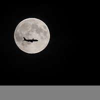 A commercial plane is silhouetted against the third and final full supermoon of 2014