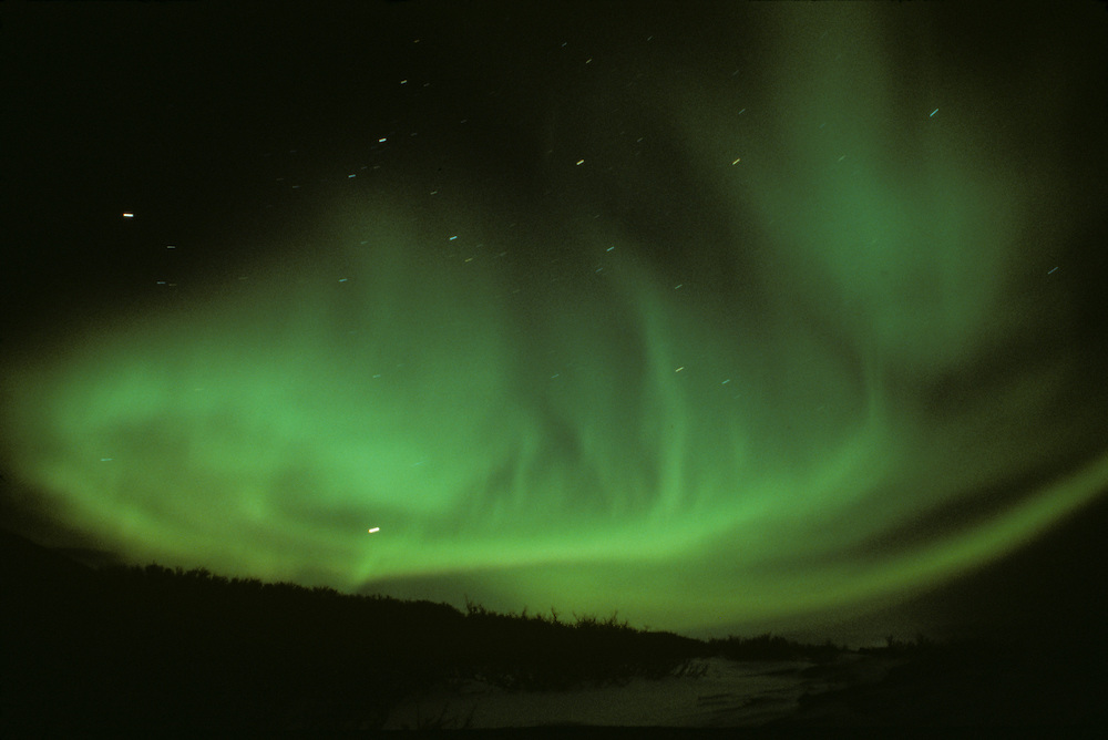 Europe, Norway, Northern lights fill the sky outside northern town of Tromso in early winter.