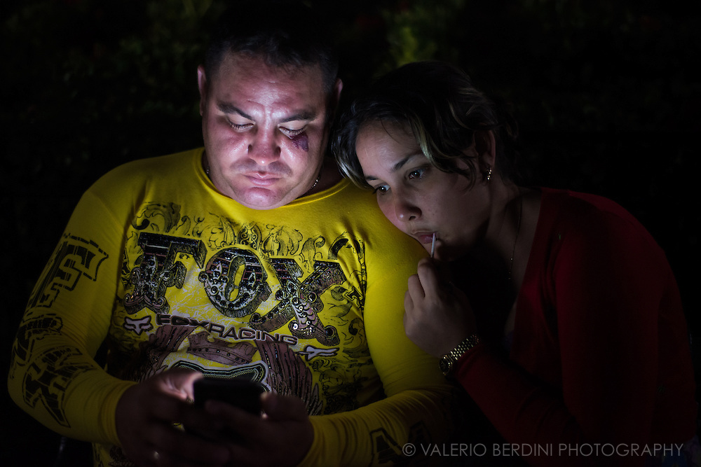A couple surfing the internet using a wi-fi point on a bench in Plaza Carillo in Trinidad de Cuba, on the night of the 26 December 2015. Trinidad had access to wi-fi for only few weeks and many Cubans are still learning how to navigate the web. These couple was aware of the photographer, but they continued in their activity. This photo was not staged.