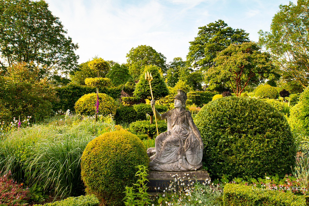 A stone statue of Britannia surrounded by topiary in the Laskett Gardens, Much Birch, Herefordshire, UK