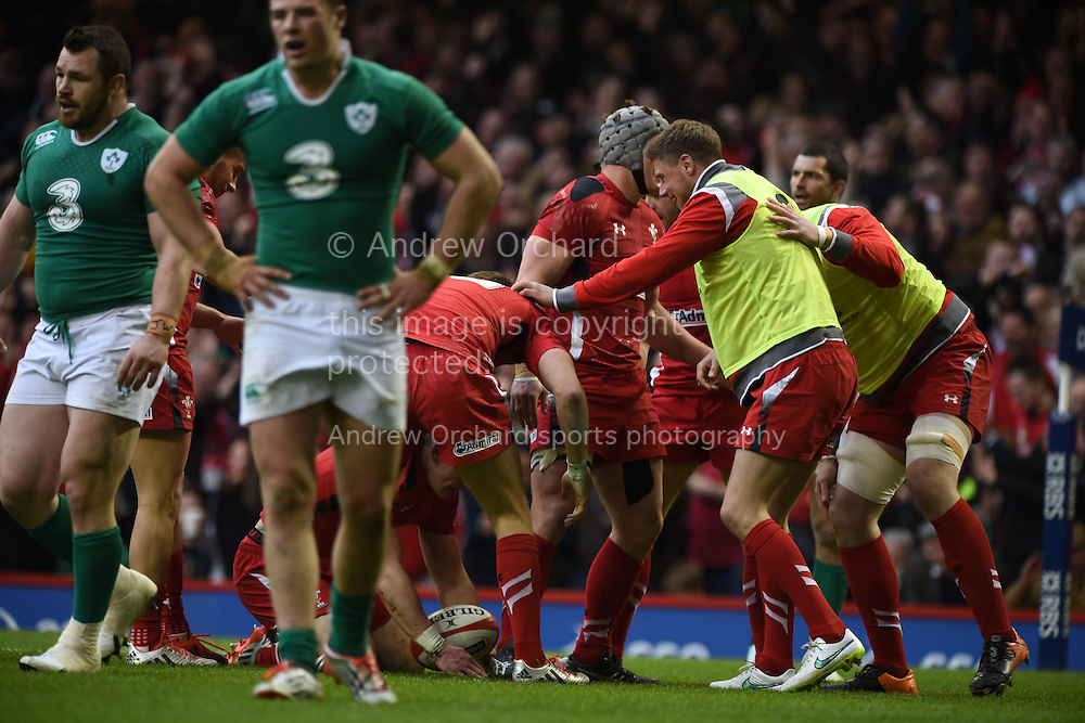 The Wales replacements celebrate with Scott Williams (on ground) after he scores his teams try.   RBS Six nations 2015 championship, Wales v Ireland  at the Millennium stadium in Cardiff, South Wales on Saturday 14th March 2015<br /> pic by Andrew Orchard, Andrew Orchard sports photography.