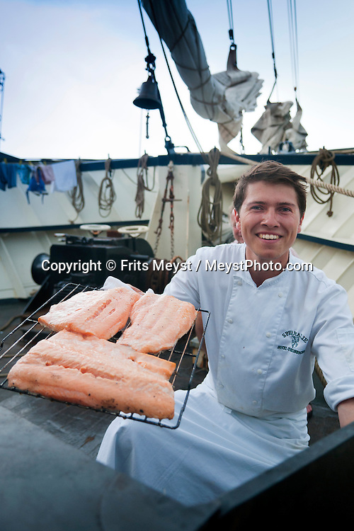 Ireland, July 2013. Chef Jelle Dam smoked his own Salmon on board.  It is the first time that Tallship Thalassa, a barquentine sailing vessel with 3 masts, sails from Belfast to Galway along the Irish coastline. While a full-rigged ship is square-rigged on all three masts, and the barque is square-rigged on the foremast and main, the barquentine extends the principle by making only the foremast square-rigged. The advantages of a smaller crew, good performance before the wind and the ability to sail relatively close to the wind while carrying plenty of cargo made it a popular rig at the end of the 19th century. Photo by Frits Meyst/Adventure4ver.com