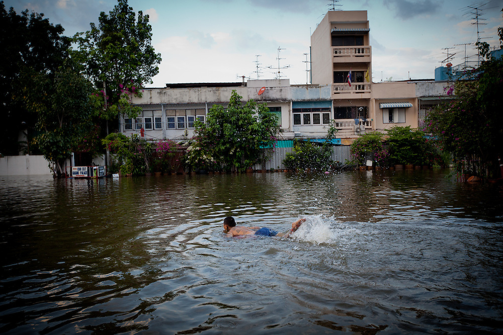 Prime Minister Yingluck Shinawatra told the crisis had now reached a critical point for Bangkok. The Chao Phraya River is already at record high level in places and many parts of the capital could be in danger by the weekend.///A man swims in a residential neighborhood already submerged with water.
