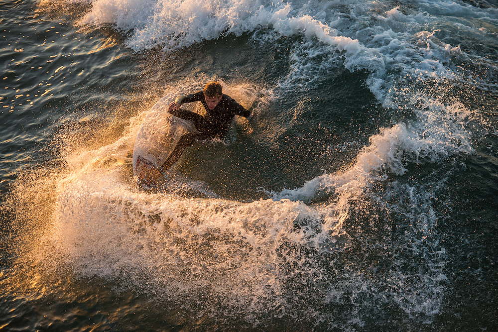 A surfing catching a wave while the sun rose in  Hungtinton Beach, California, on November 3, 2016.