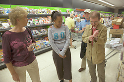 Group of day service users with learning disability accompanied by Day Service Officer shopping at the  supermarket,