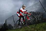 Male athlete training for a fall cyclo-cross race on a cold cloudy day.