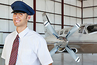 Portrait of happy young male pilot standing in front of airplane