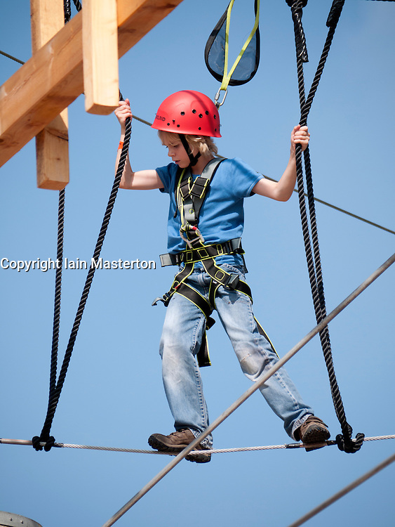 Young boy climbing on modern  new outdoor adventure playground featuring multi-level climbing and obstacle courses in Berlin Germany