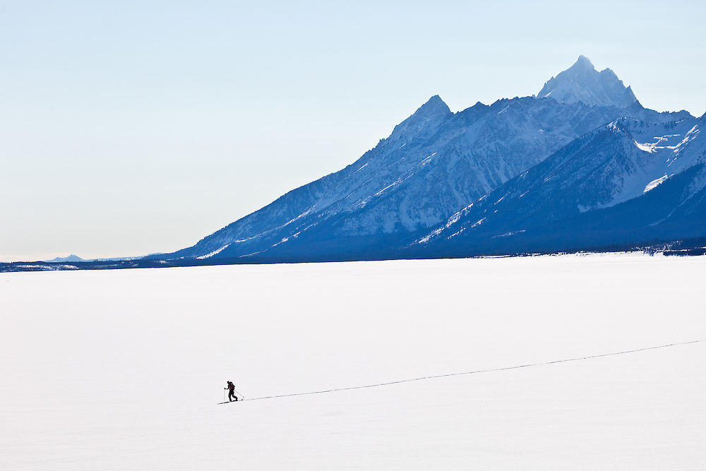 Man skis across a frozen  Jackson Lake in Teton National Park in Wyoming near Jackson Hole after summiting and skiing a Teton Peak