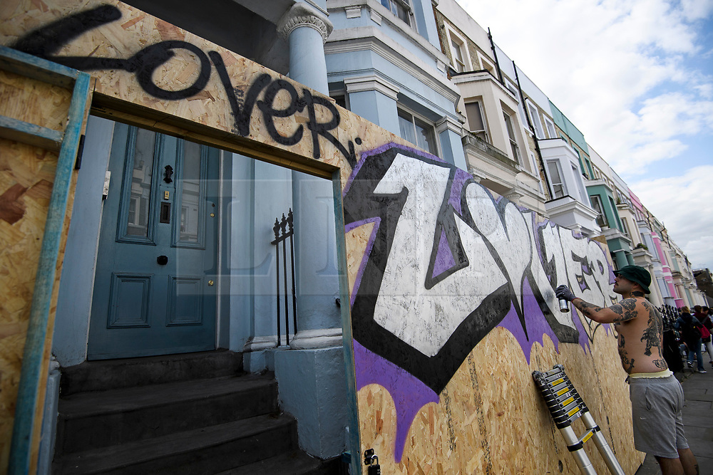 © Licensed to London News Pictures. 25/08/2018. London, UK. A graffiti artists paints on to boarding protecting a residential property in Notting Hill, West London ahead of the 2018 Notting Hill Carnival which starts tomorrow (Sunday). Up to 1 million people are expected to attend this weekend's event that is one of the worlds largest street festivals. Photo credit: Ben Cawthra/LNP