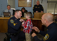 Detective Benjamin Black getting pinned by his son Ryan during the Laconia Police Commissioners meeting Thursday afternoon at City Hall.  (Karen Bobotas/for the Laconia Daily Sun)
