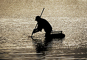 Man clamming with the help of a clam rake and a floating basket.