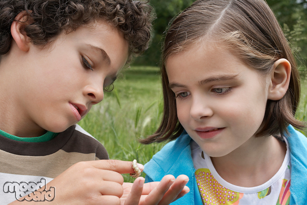 Brother and sister (7-9) examining caterpillar outdoors