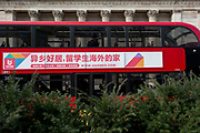A London bus carrying banner advertising written in Chinese characters for the worldwide online property rental and listings site website UHOMES, and passes the columns of the Bank of England on Threadneedle Street in the heart of the City of London, the capital's financial district, on 11th March 2020, in London, England.