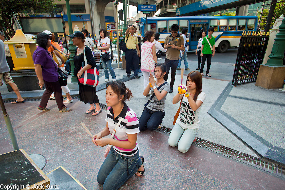 25 MARCH 2010 - BANGKOK, THAILAND: People pray at the Erawan Shrine in Bangkok. The Erawan Shrine (Thai: San Phra Phrom) is a Hindu shrine in Bangkok, Thailand that houses a statue of Phra Phrom, the Thai representation of the Hindu creation god Brahma. The Erawan Shrine was built in 1956 as part of the government-owned Erawan Hotel to eliminate the bad karma believed caused by laying the foundations on the wrong date. The hotel's construction was delayed by a series of mishaps, including cost overruns, injuries to laborers, and the loss of a shipload of Italian marble intended for the building. Furthermore, the Ratchaprasong Intersection had once been used to put criminals on public display. An astrologer advised building the shrine to counter the negative influences. The Brahma statue was designed and built by the Department of Fine Arts and enshrined on 9 November 1956. The hotel's construction thereafter proceeded without further incident.      PHOTO BY JACK KURTZ