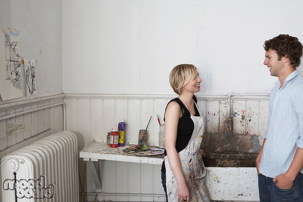 Two college students chatting by sink in art studio