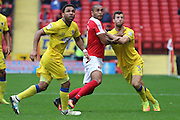 Charlton Athletic striker Josh Magennis (9) is put under pressure from AFC Wimbledon defender Jon Meades (3) and AFC Wimbledon striker Andy Barcham (17) during the EFL Sky Bet League 1 match between Charlton Athletic and AFC Wimbledon at The Valley, London, England on 17 September 2016. Photo by Stuart Butcher.