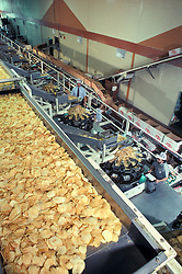 snack Food manufacturing industiral plant workers oversee potato chip assembly line