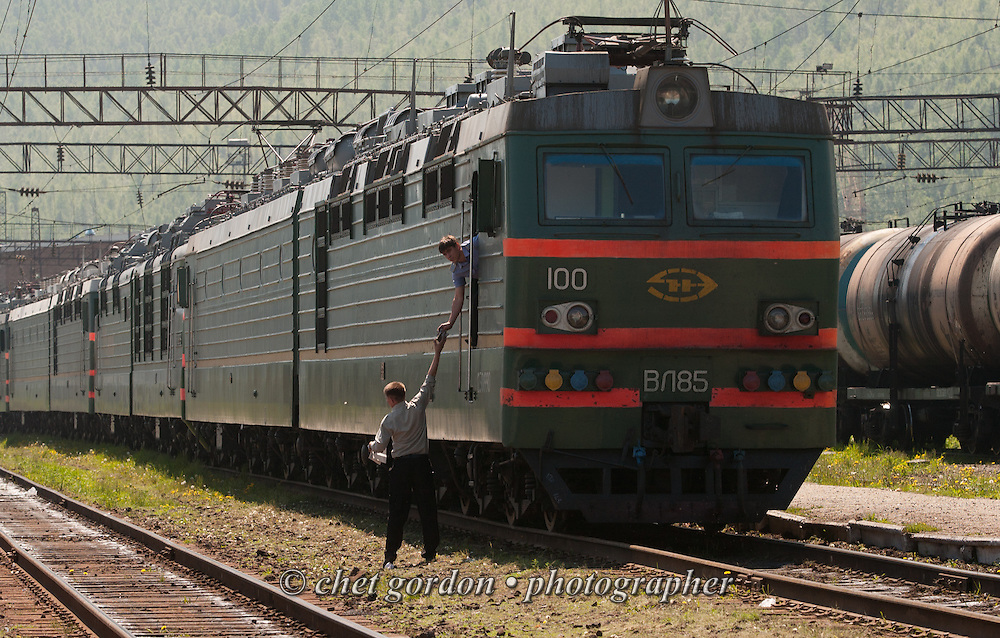 A railway worker hands a drink to a train engineer in the locomotive of his train at Slyudyanka Station near Lake Baikal, Siberia - Russian Federation on June 15, 2005.
