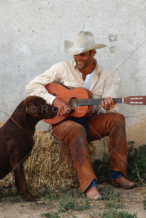 cowboy with his guitar and brown lab dog