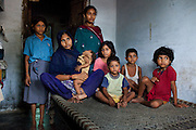 """Sitara (aged 35, 2nd from left), sits with her 7 children (5 daughters & 2 sons) as she breastfeeds her 8 month old baby girl in a village in Allahabad, Uttar Pradesh, India. """"I wish that I could stop getting pregnant but our religion says that children are a gift of God."""" Sitara is an illiterate muslim lady whose husband works as a vegetable vendor in the local village market. They have resisted all advises of permanent sterilization from the local village-level health workers. Children from left to right : Roshni (10), Tamanna (8 months), Chandni (14), Sufia (8), Asif (3), Ajman (5), and Rani (7). Photo by Suzanne Lee / Panos London"""