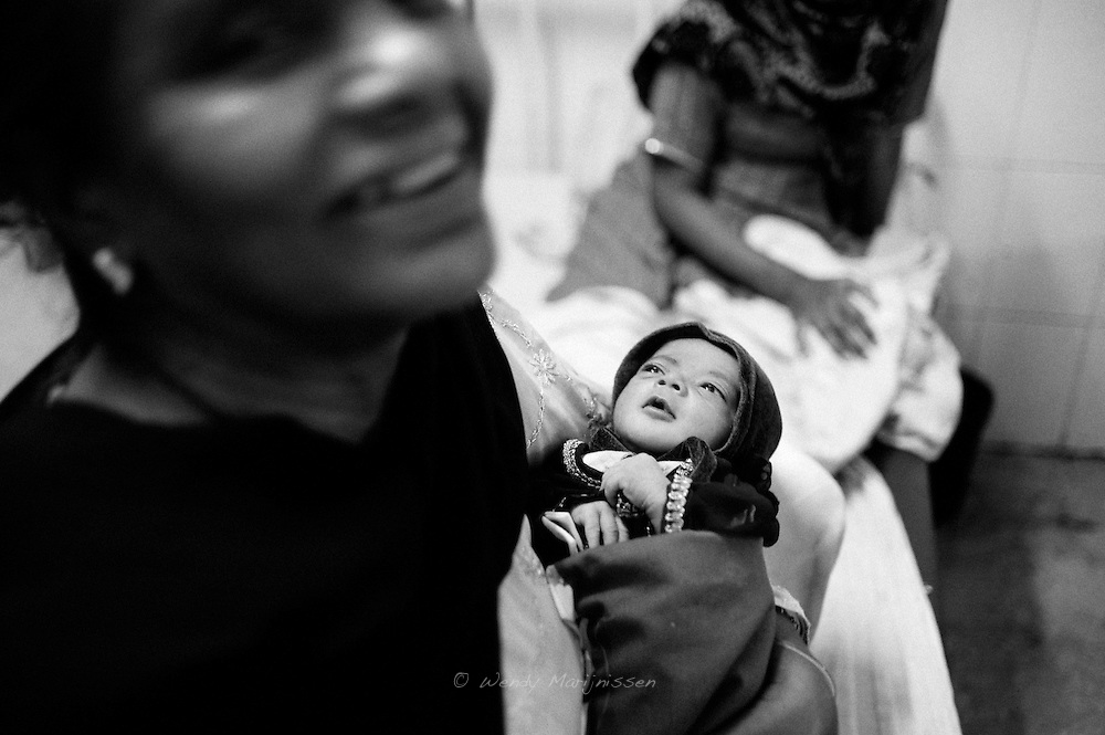 A mother-in-law proudly shows her newborn granddaughter while Dr. Musarat is doing rounds in the ward. Karachi, Pakistan, 2010