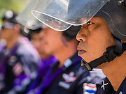 04 DECEMBER 2013 - BANGKOK, THAILAND: Thai riot police form up on the plaza in front of Royal Thai Police Headquarters in Bangkok. Several hundred anti-government protestors tried to occupy Royal Thai Police Headquarters on Rama I Road in central Bangkok Wednesday. The protest was one of the continuing protests against the government of Prime Minister Yingluck Shinawatra. Police commanders allowed protestors to tear down police barricades and ordered riot police to lay down their shields. Protestors then chanted anti-government slogans and called on police to turn against the government before forming a motorcade and leaving the area. Anti-government protests have gripped Bangkok for nearly a month and protestors vow to continue their actions. Protests Wednesday were much smaller and more peaceful than protests earlier in the week.      PHOTO BY JACK KURTZ
