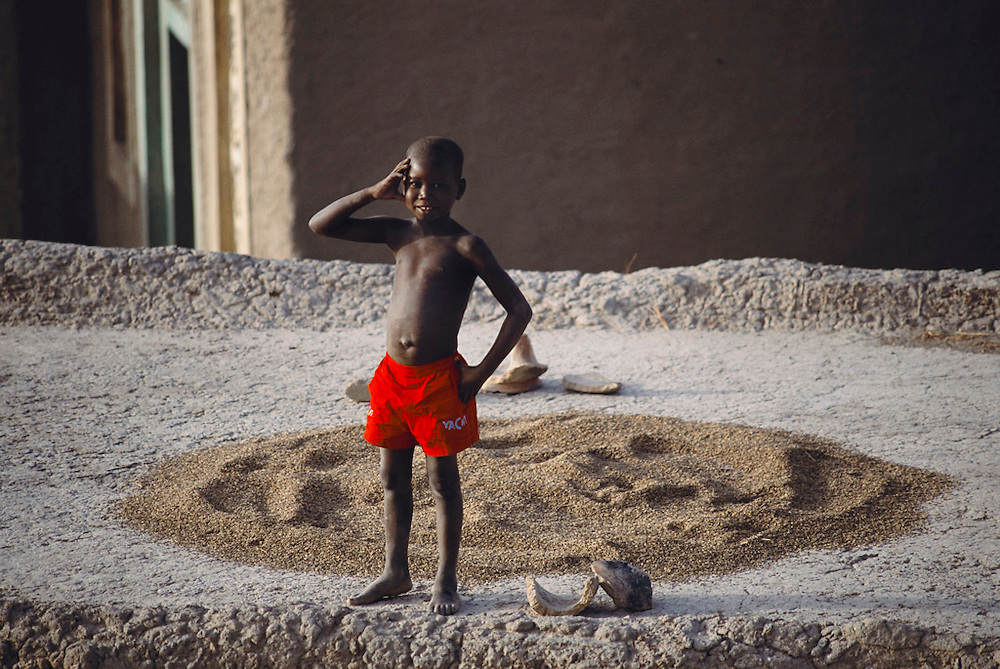 A young boy looks bemused as he stands on the roof of his mudbrick home in the W. African village of Kouakourou, Mali. A mound of grain is drying in the sun behind him. Material World Project.