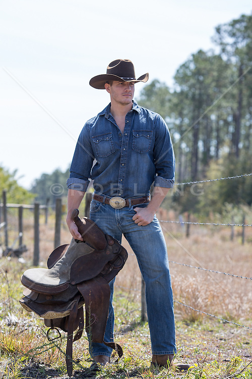 hot rugged cowboy holding a saddle outdoors in rural America handsome rugged cowboy outdoors