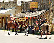 "Two cowgirls on horseback trying to coax a longhorn to move on down a street in Bandera, Texas. NOTE: Click ""Shopping Cart"" icon for available sizes and prices. If a ""Purchase this image"" screen opens, click arrow on it. Doing so does not constitute making a purchase. To purchase, additional steps are required."
