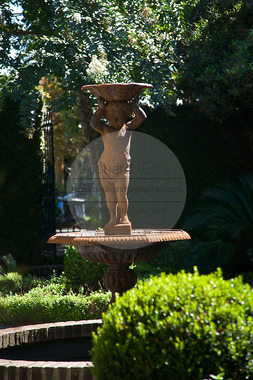Traditional cherub fountain in the garden of a historic home in Charleston, SC.