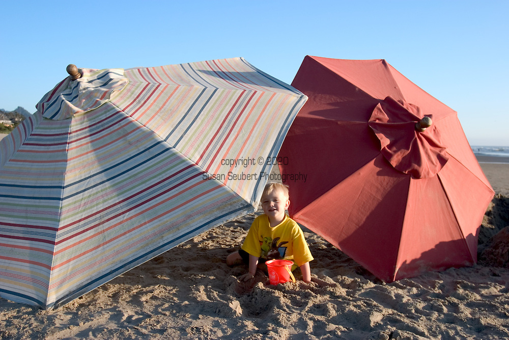 A young boy playing under colorful umbrellas on Cannon Beach, Oregon.
