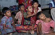 Rajasthani children watching a traditional television programme on a tv set in the couryard oftheir home (Rajasthan, India)
