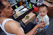 Panjiayuan weekend market. Shop owner feeding his little baby boy.